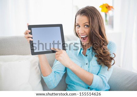 Euphoric woman showing her tablet screen sitting on cosy sofa - stock photo
