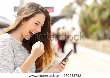 Euphoric woman watching her smart phone in a train station while is waiting  - stock photo