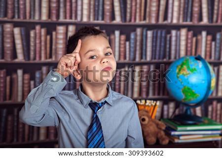 Eureka, first-grader boy thoughtfully rubbing his head - stock photo