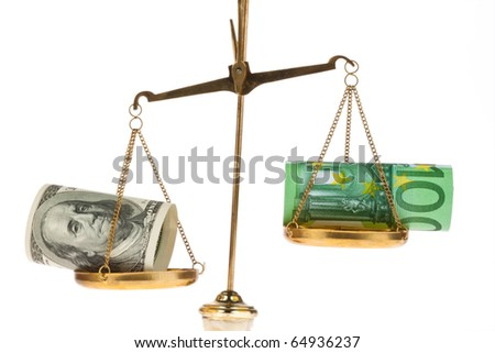 Euro banknotes and dollar on scales before a white background - stock photo