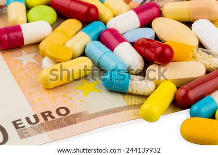 euro banknotes and tablets, symbol photo for costs of medicines and health insurance. - stock photo