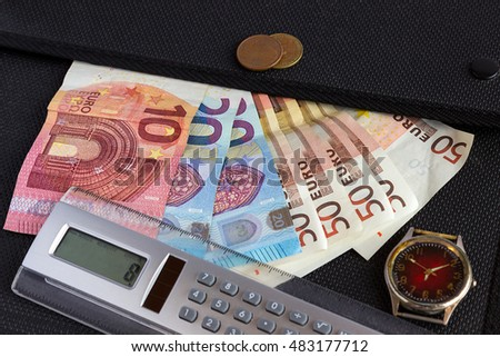 Euro banknotes, calculator and clock lie on the black folder for documents. Concept - money, finance.
