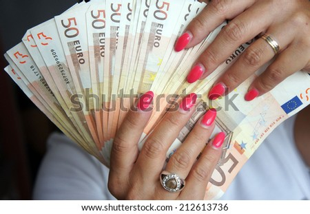 Euro banknotes in female hand - stock photo