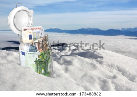 Euro banknotes in jar in the snow on the mountain top - stock photo