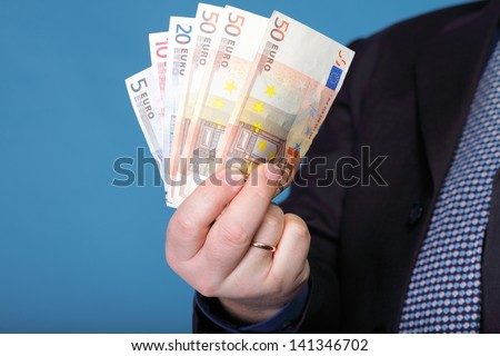 Euro banknotes in male hand on blue background