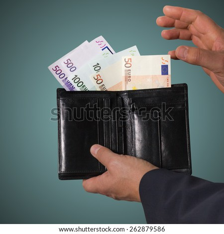 Euro banknotes in the black wallet isolated on blue background. Man holding wallet with money.  - stock photo