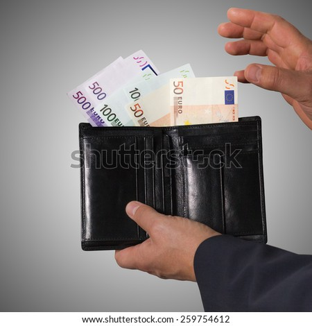 Euro banknotes isolated on a grey background. Man counts money euro. Man hides money in his wallet. - stock photo