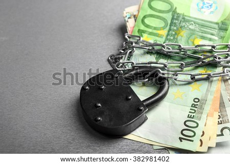 Euro banknotes with lock and chain on gray background