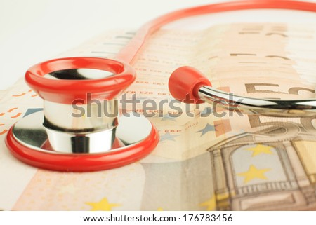Euro banknotes with red stethoscope close-up  - stock photo