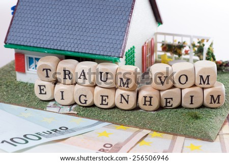 Euro Banknotes with Wooden cubes and the german words dream of home ownership / Home Ownership - stock photo