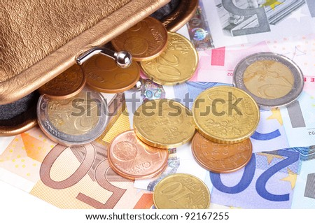 Euro bills and coins coming out of a wallet