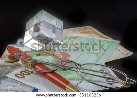 Euro bills, Coins, Pen, and Glasses on black background. Business and Office concept