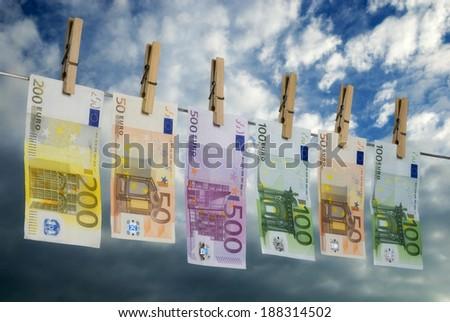 Euro bills hanging on a washing line, symbolizing money laundering. - stock photo