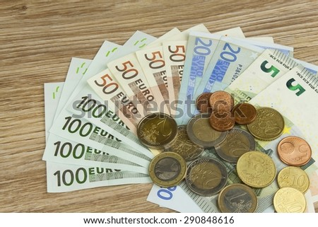 Euro coins and banknotes on the table. Detailed view of the legal tender of the European Union, EU. The uncertain future of the euro. - stock photo