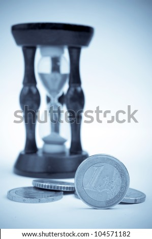 Euro coins and hourglass in the background - blue toned image - stock photo