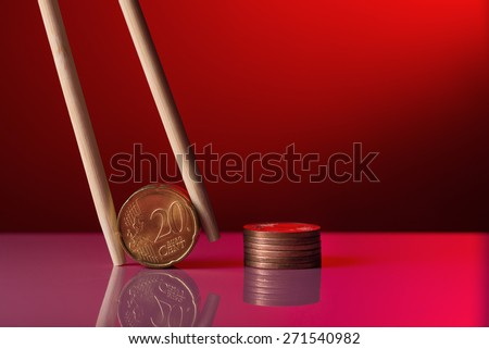 Euro coins held by chopstick over red background - stock photo