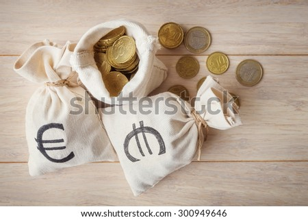 Euro coins in money bags, top view - stock photo