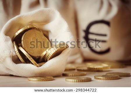 Euro coins in open money bag - stock photo