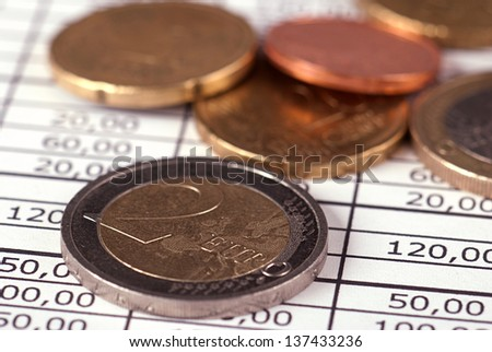 Euro coins lying on the financial schedule