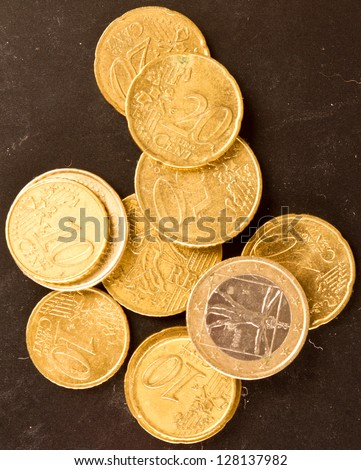 Euro coins on dirty dark background with goldish light effect - stock photo