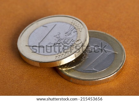 Euro coins on the brown surface. - stock photo