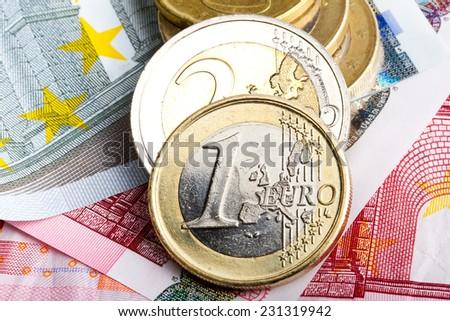 Euro coins over banknotes - stock photo
