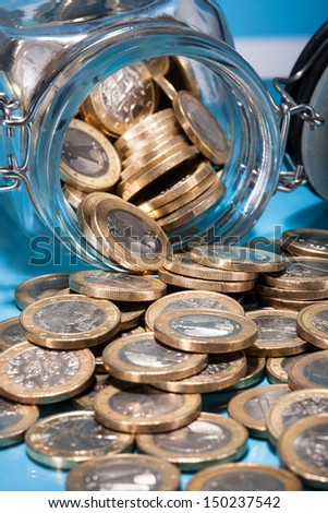 Euro Coins Spilling From A Money Jar - stock photo