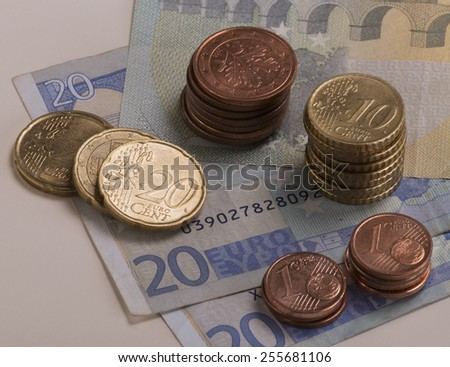 Euro coins stacked on 20 Euro bills and a 5 Euro bill.