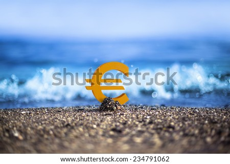 Euro currency icon is standing on the wavy sea side - stock photo