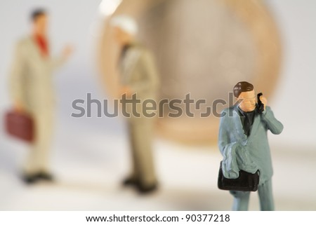 Euro - Divergent Views, macro of miniature businesspeople standing in front of a Euro coin with one man talking on his phone facing the other way - stock photo