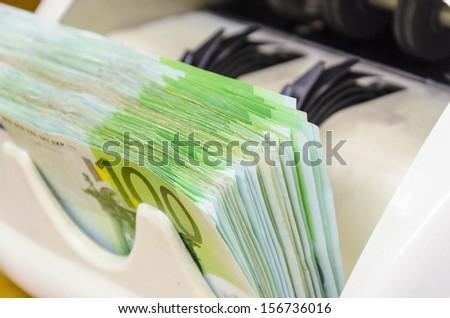 Euro (EUR) banknotes of 100 on money counter machine - legal tender of the European Union - stock photo