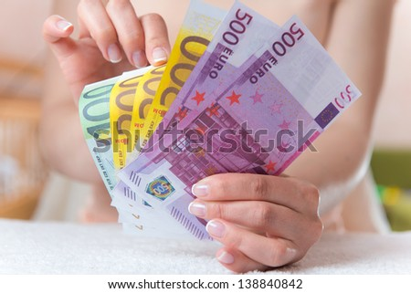 Euro in beautiful female hands. Money in focus - stock photo