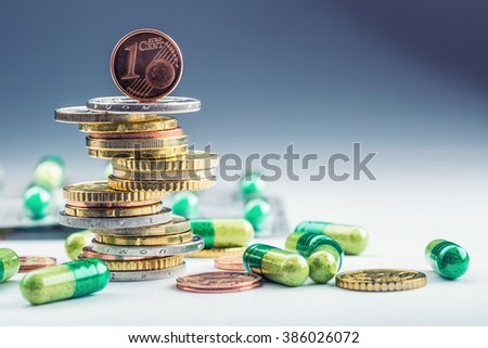 Euro money and medicaments. Eurocoins and pills. Coins stacked on each other in different positions and freely pills around scattered. Toned image. - stock photo