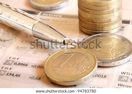 Euro money coins and silver colored ball pen on top of stock market chart - stock photo