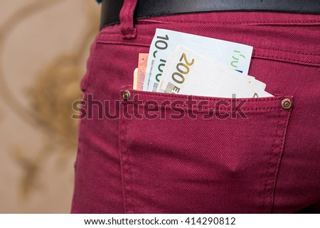 Euro notes in red jeans pocket - stock photo