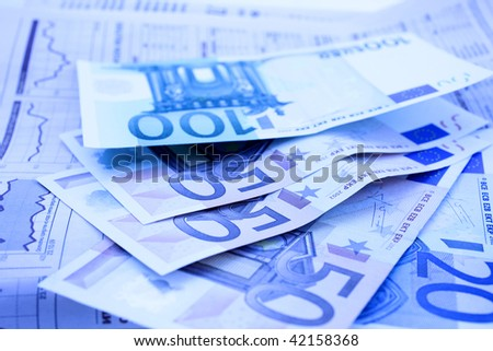 euro notes on a financial newspaper in blue tones. closeup. small GRIP. - stock photo