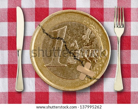 Euro on tablecloth with knife and fork - stock photo