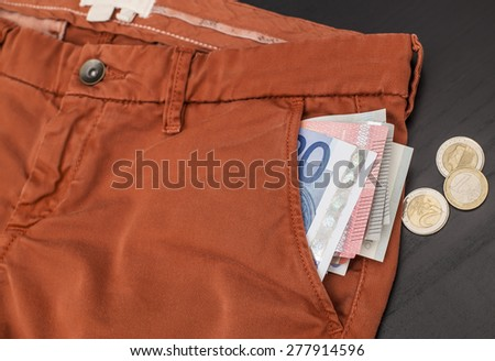 euro paper money sticking out of his trouser pocket and coins lay on a black wooden table - stock photo