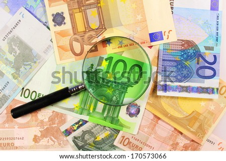 Euro paper notes. Perfect for any financial, commerce, treasury or banking needs. Magnifying glass over Euros - stock photo