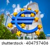 Euro sign at European Central Bank headquarters in Frankfurt, Germany with dark dramatic clouds symbolizing a financial crisis - stock photo