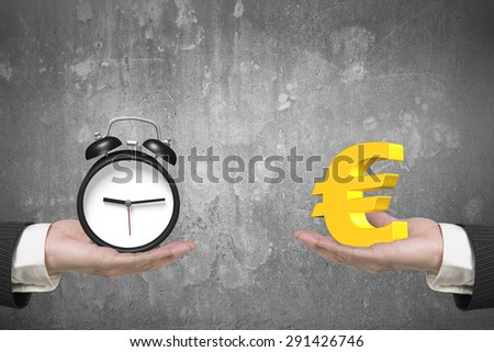 Euro symbol on one hand and alarm clock on another hand, with concrete wall background, concept of deal and time. - stock photo