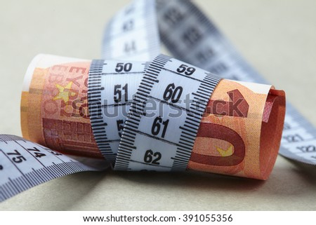 euro with measuring tape - stock photo