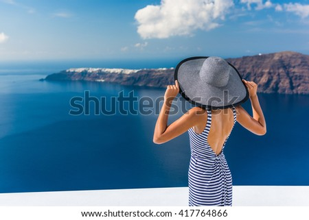 Europe summer vacation travel destination luxury living woman looking at view of Mediterranean Sea and Santorini island Oia village. Elegant tourist lady in fashion back dress and floppy sun hat. - stock photo