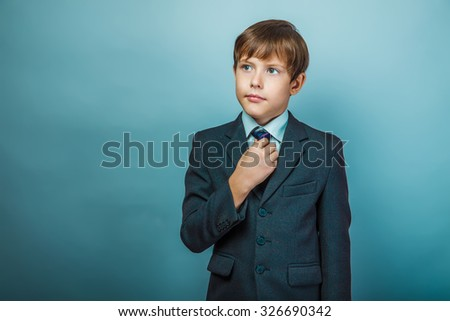 European appearance teenager boy in a business suit straightens tie businessman, confidence, work
