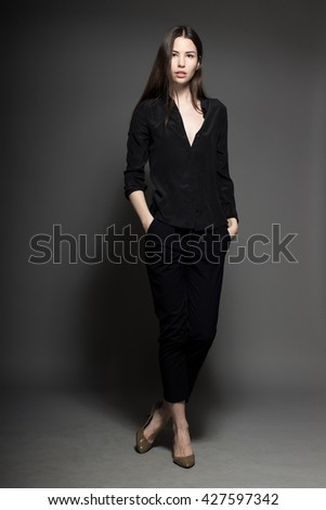 European attractive sexy fashion model with natural brunette hair, posing in studio, wearing black shirt, dark background, beauty photo shot, retouched image - stock photo