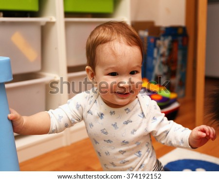 European baby standing on his feet in the children's room and smiling - stock photo