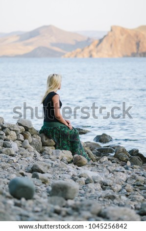 European blond girl resting on the beach. Summer landscape with sea and mountain views. Sunny weather in the morning