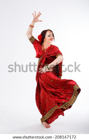 european brunette girl in red indian saree dancing with her hands and flying skirt in studio on gray background - stock photo