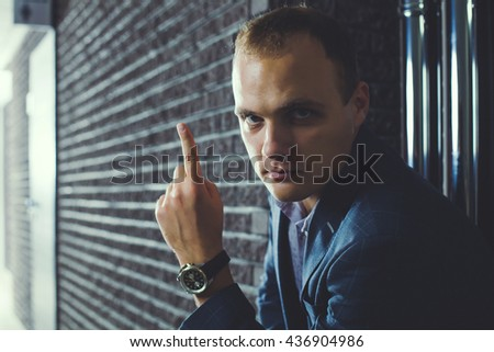 European businessman is sitting in the corridor of office and thinks. - stock photo