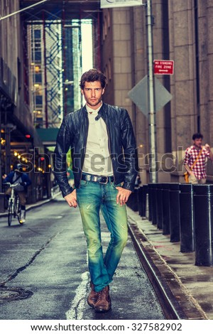 European businessman traveling in New York. Wearing black leather jacket, white undershirt, blue jeans, brown boot shoes, a young guy with beard walking on narrow wet street after raining,   - stock photo